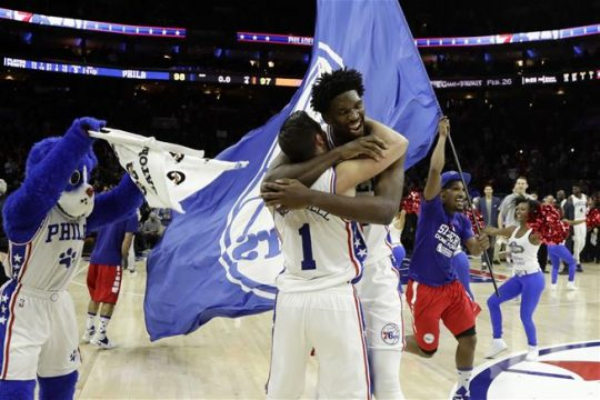 (Photo Credit: AP Photo/Matt Slocum) Embiid and McConnell celebrating a last second win over New York.